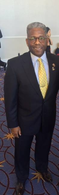 Allen West looking great in his custom fit suit, polished shoes, and yellow necktie.
